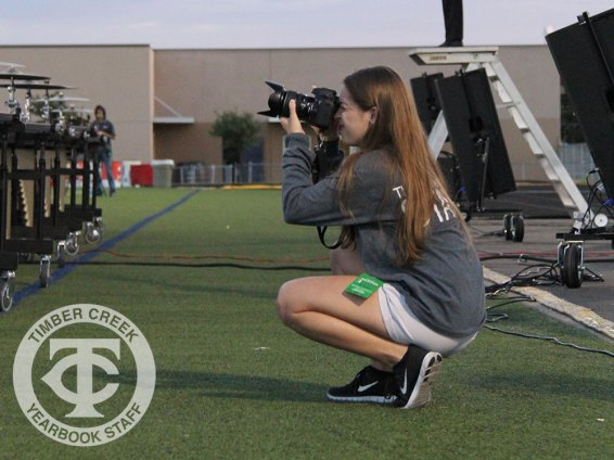 The Creek Yearbook photographer Taylor Deker takes photos from the sideline.