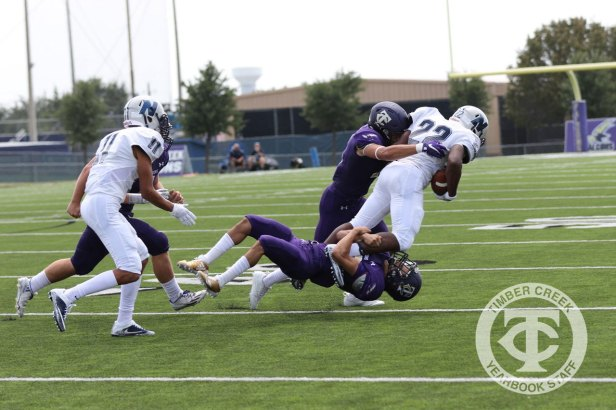 Two Timber Creek defenders tackle an Irving Nimitz player during the Sept. 2, 2017 home opener. (Photo by Yearbook Editor Taylor Deker.)