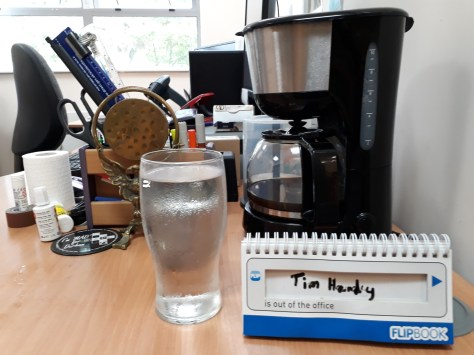 pint glass, humorous desk sign and a coffee machine