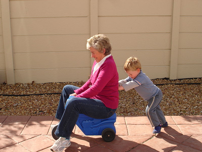 kid pushing Grandma on toy tractor