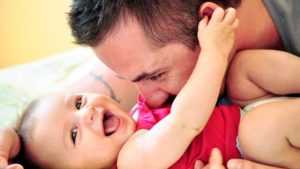 Parenting Today Versus The Past - Father kissing baby