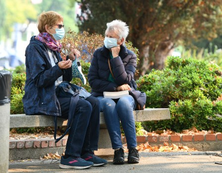 Women wear masks as they talk on a bench outside of St. Paul's Episcopal Church in downtown Benicia on Friday. (Chris Riley/Times-Herald)
