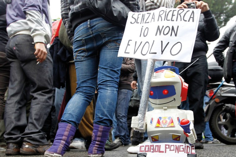 Toy robot holding 'Without research I can't evolve' sign, Italy