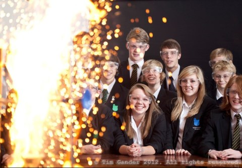 School science experiment with big yellow flash of flame with pupils looking on