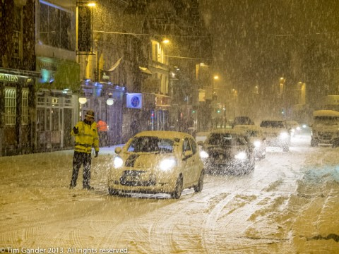 In Bolton a police officer directs traffic in heavy snow