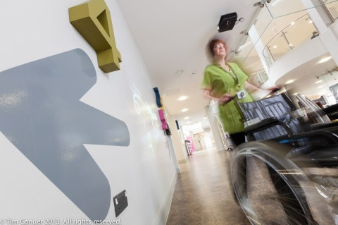 A nurse is blurred as she pushes a wheelchair at Frome Medical Centre with smooth plastered and painted wall dominant to the left of the frame