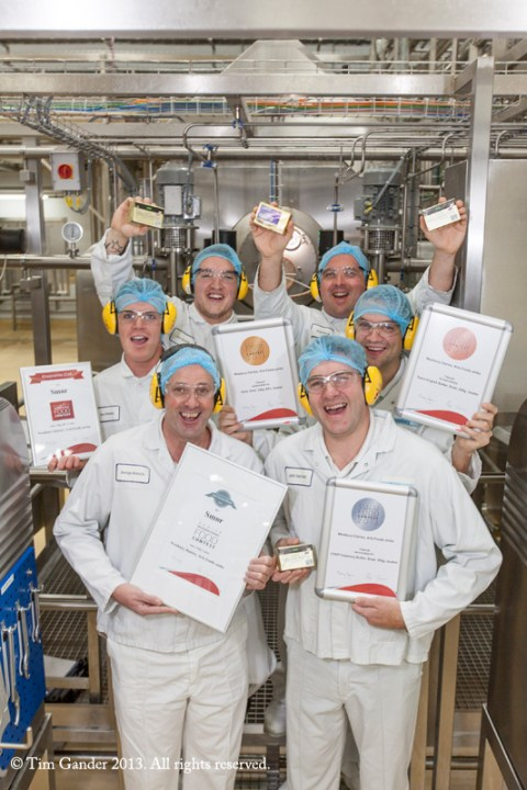 Westbury Dairy production team holding butter and certificates while standing on the production floor.