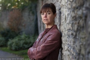 Frome-based author Sally M Gander poses by a stone wall in Frome