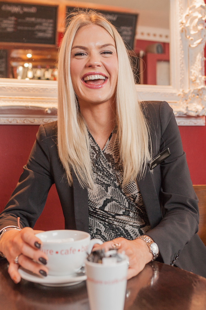 Jody Brown of Jolly's store in Bath is seated in her favourite cafe in Bath, laughing to camera.