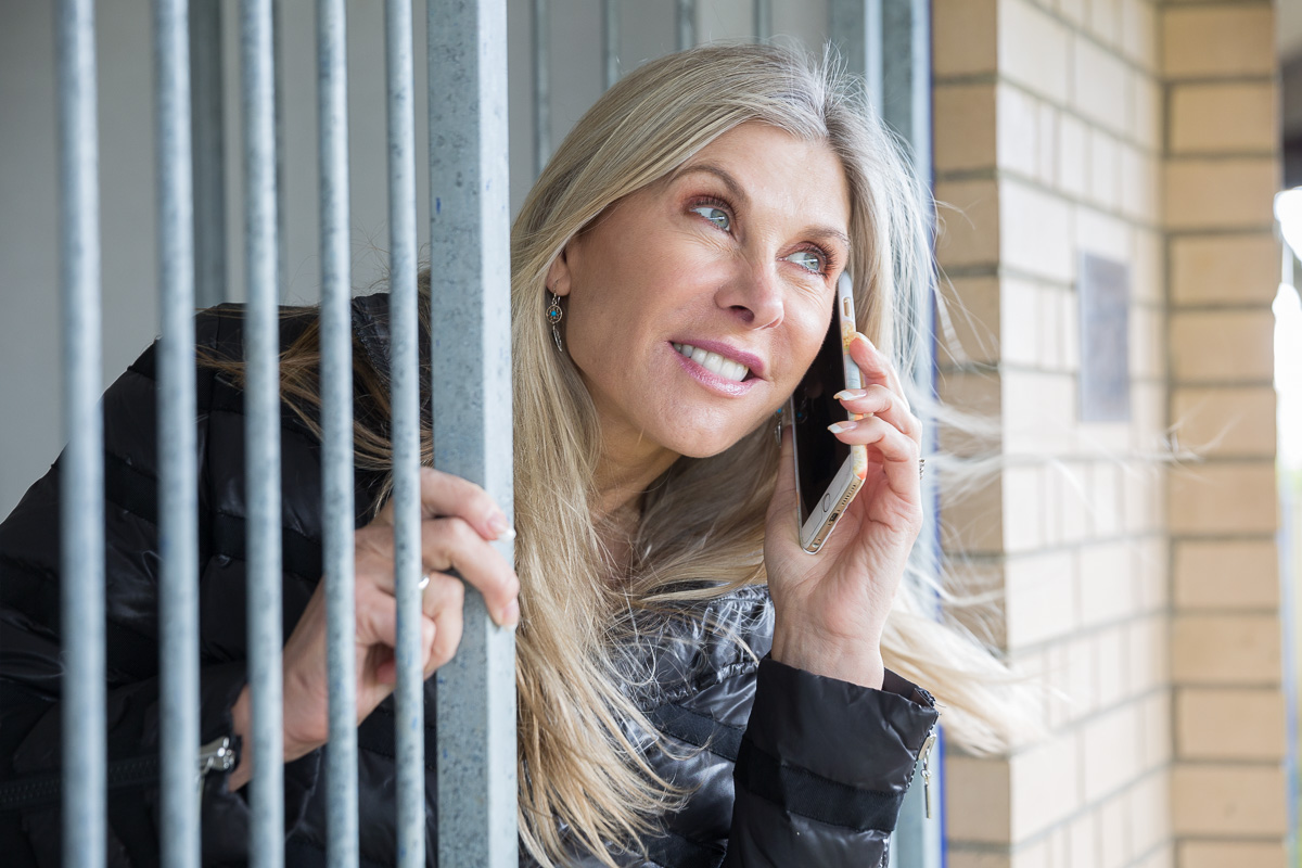 Olympic swimmer Sharron Davies leans out of the open gate of a dog kennel while holding a mobile phone to her ear.