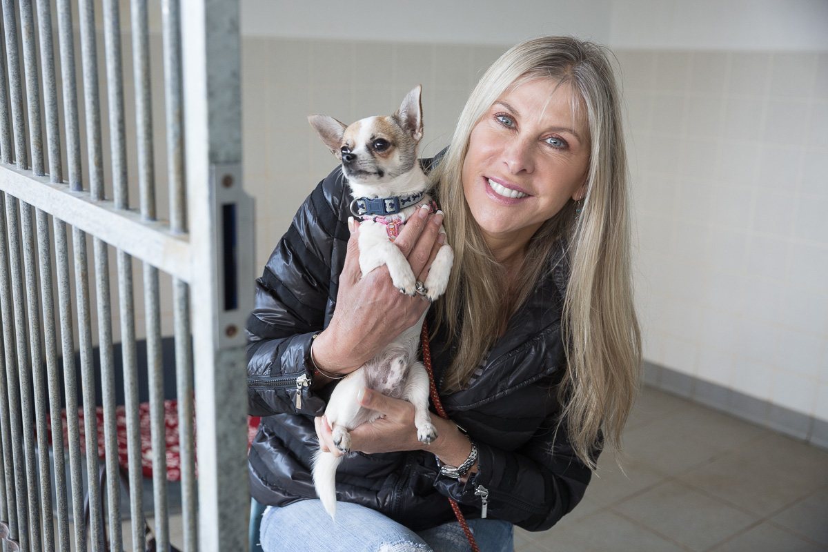 Olympic swimmer Sharron Davies holds a small dog in her hands and smiles to camera.