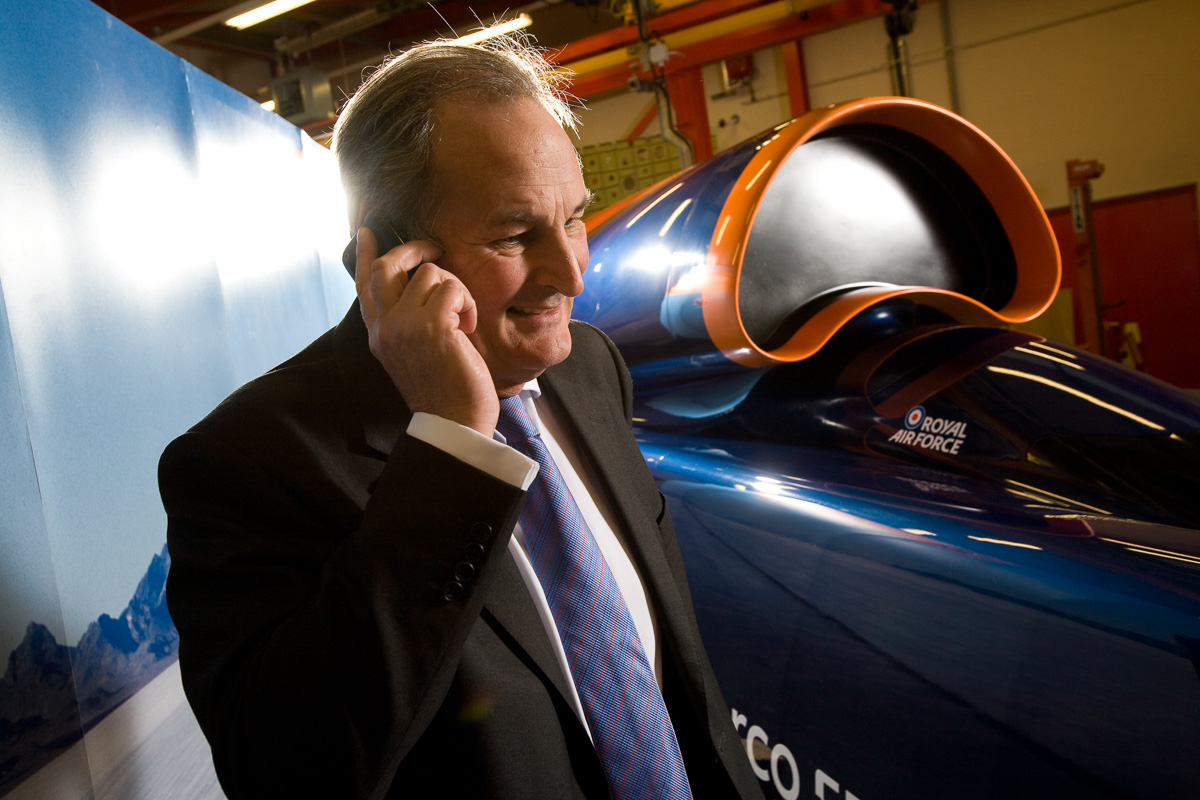 Richard Noble of the Bloodhound Super Sonic Car in talking on a mobile phone with a model of Bloodhound in the background.