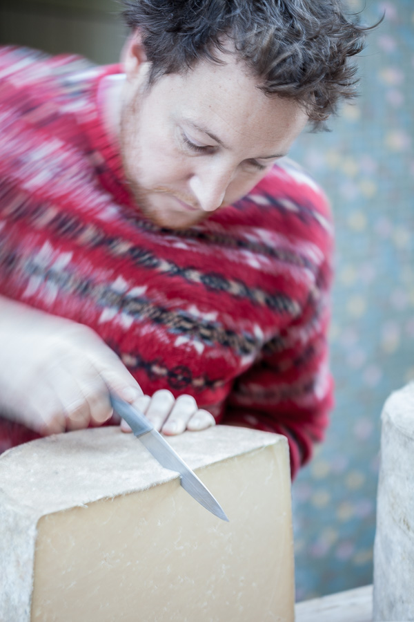 Award-winning cheesemaker Tom Calver of Westcombe Dairy slices into a round of cheese at Frome Sunday market.