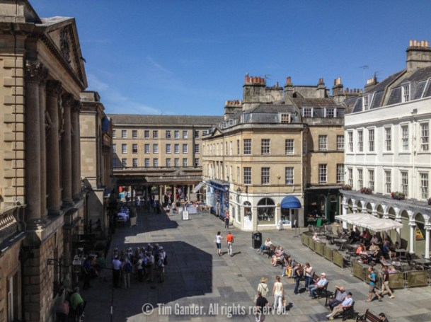 A high-level view of Bath Abbey Churchyard, taken from above the abbey door on a sunny day.