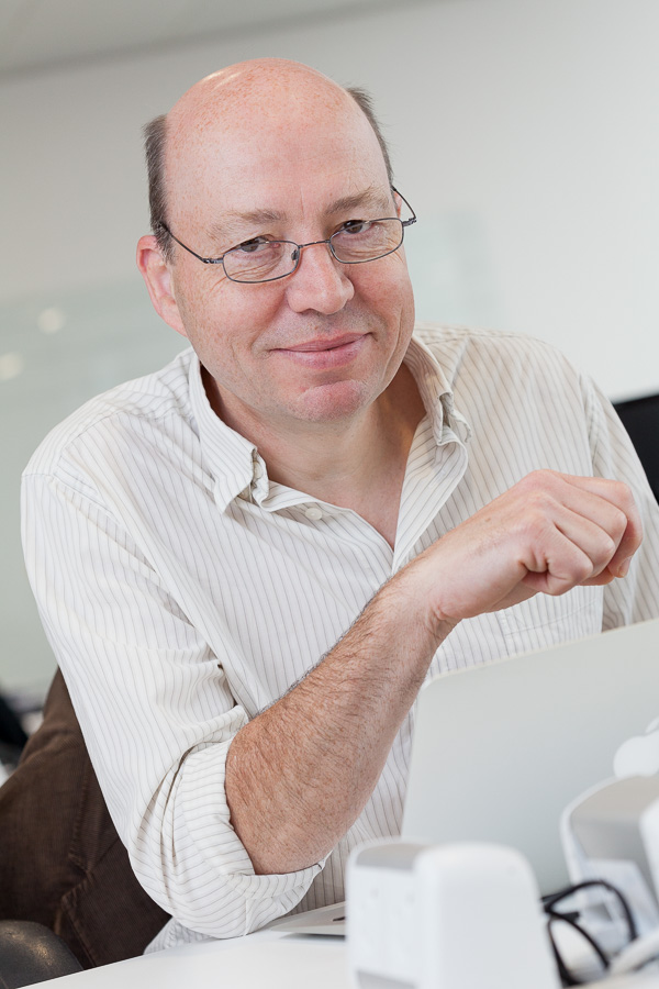 Ben Morris of Connected Digital Economy Catapult at his desk in London, smiling to camera while seated at his desk.
