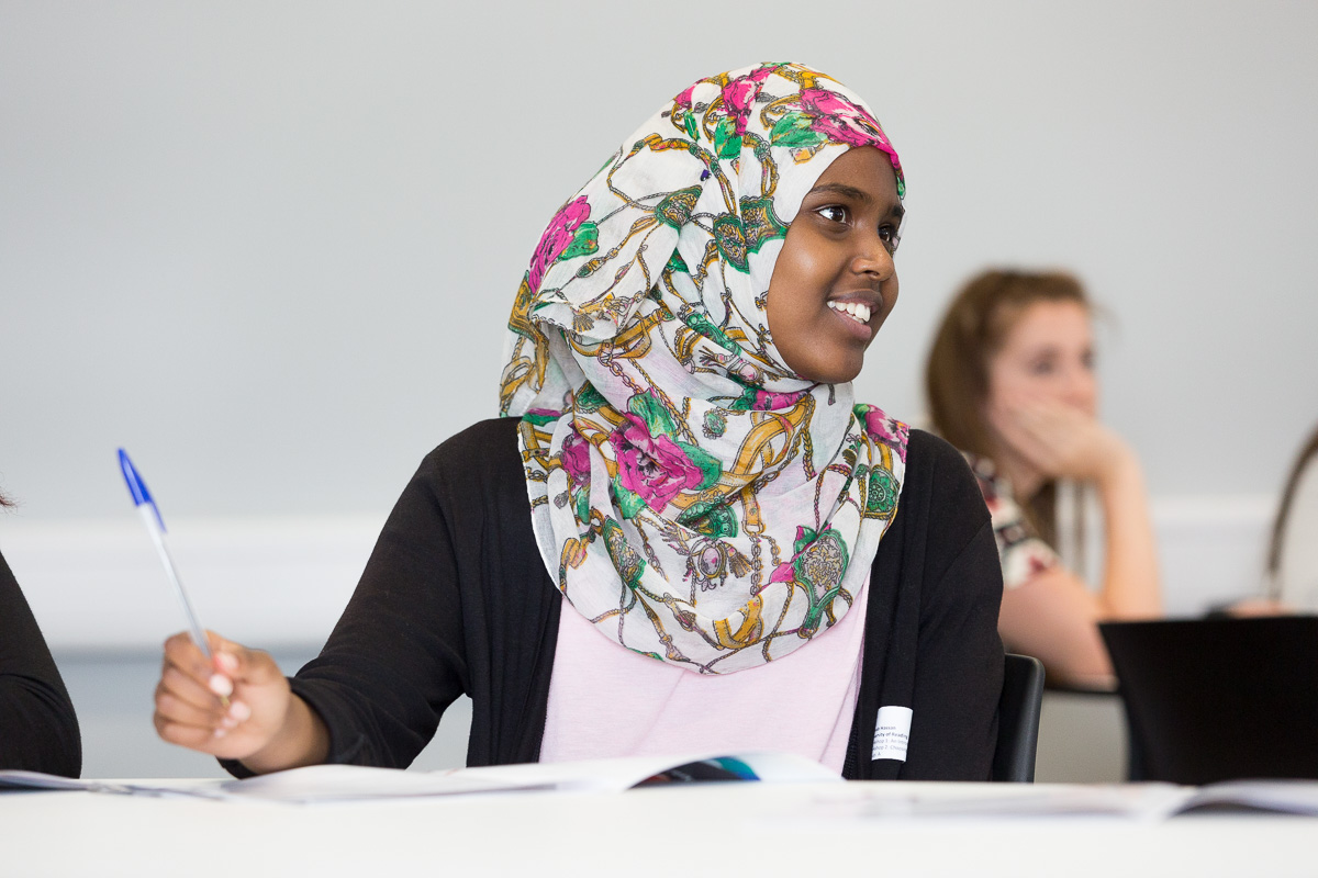 A young female student in headscarf, seated at a desk in a lecture room, smiles to someone off camera.