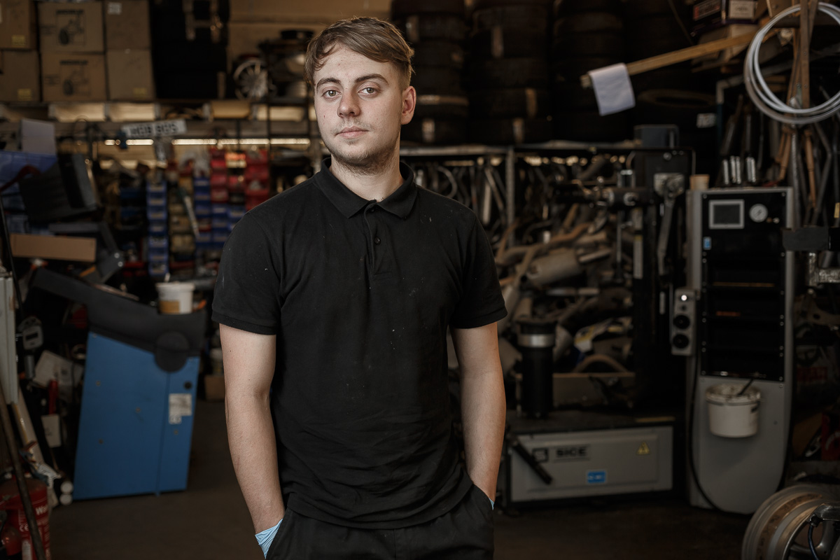 Half-length portrait of tyre fitter Ashley standing in the workshop surrounded by tools, equipment and car spares.