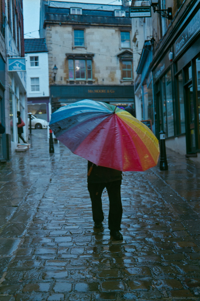 A man battles with a multi-coloured umbrella as he walks down a cobbled street in Frome, Somerset.