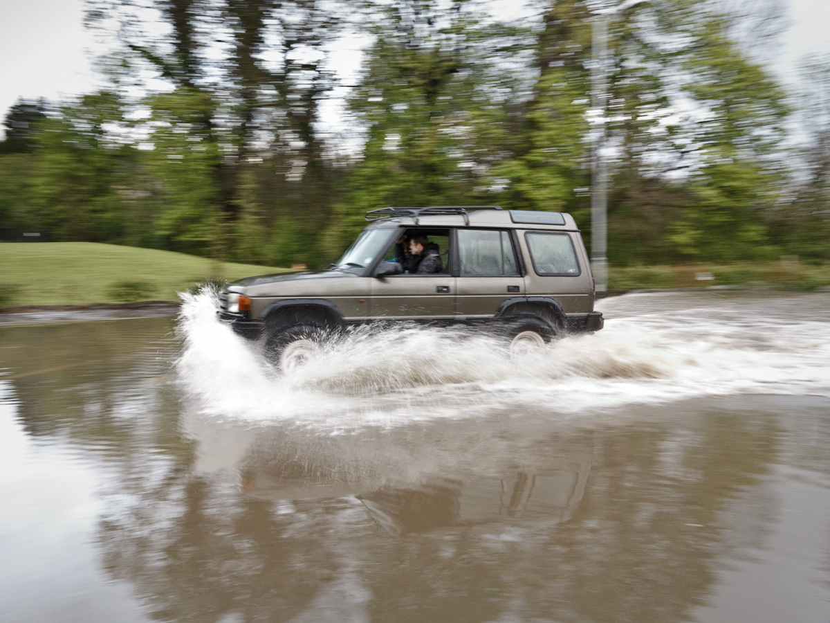 A range Rover is driven at speed through flood water.