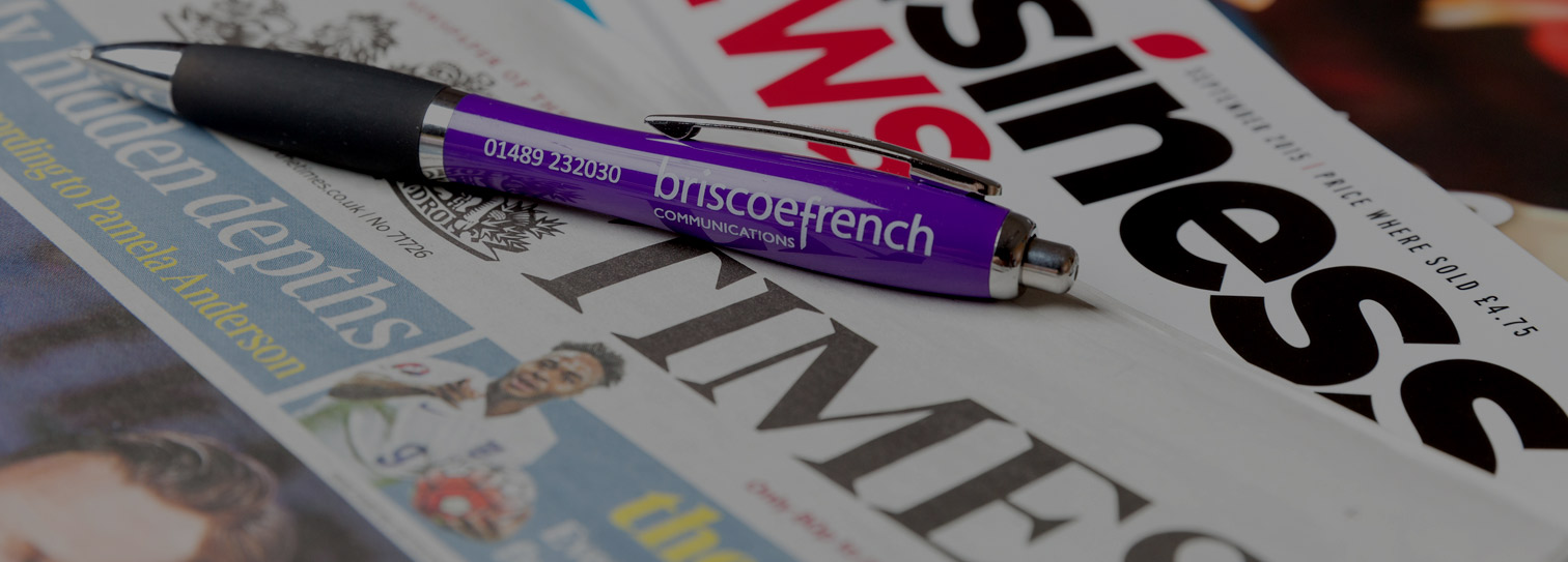 A Briscoe French branded pen lies on a pile of newspapers and magazines to illustrate the Briscoe French public relations service.