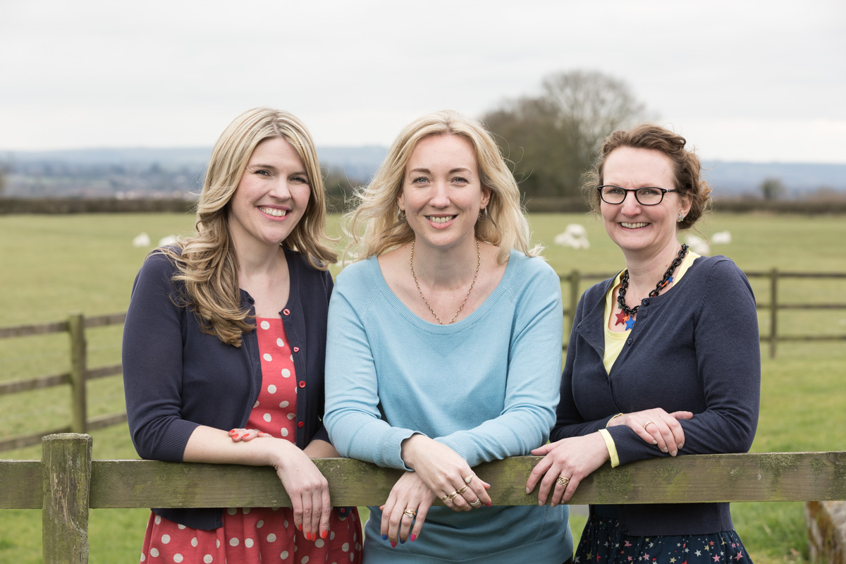 Helen Rimmer, Debbie Clifford and Michelle Gordon-Coles of Tea for Three Marketing and Communications together, looking over a wooden field gate to camera with a field of sheep behind.