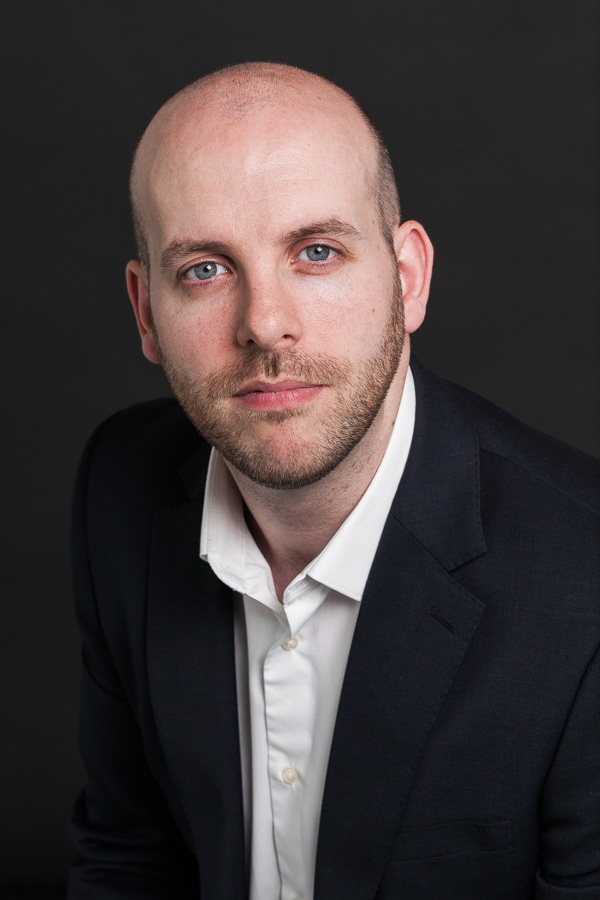 Headshot of Matt Leipnik of Digital Catapult, London non-smiling, against black.