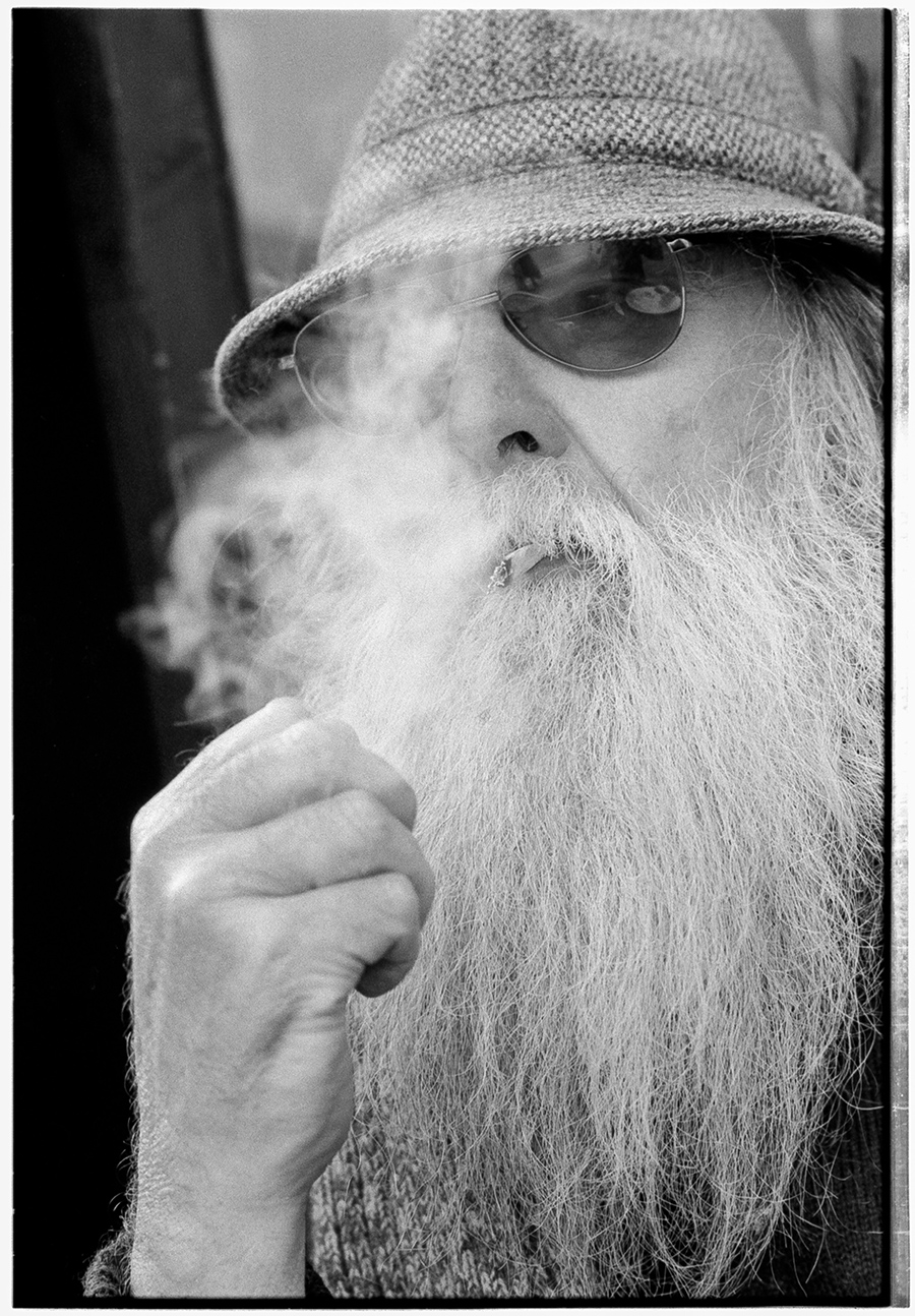 Close-in portrait of a white-bearded gentleman wearing a tweed hat and dark sunglasses and smoking a rolled cigarette, drawing on his cigarette and puffing out smoke.