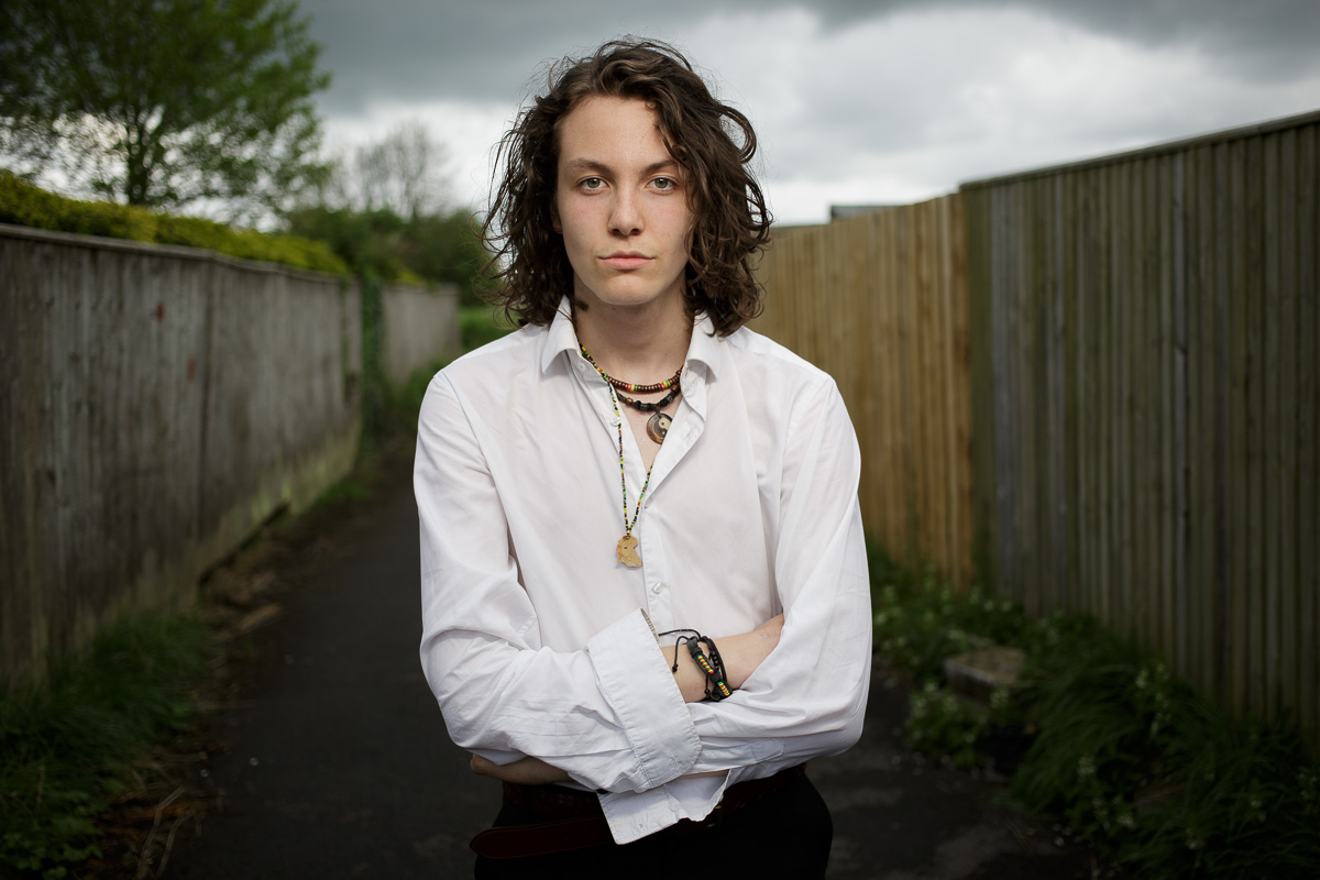 Test photo with Joe Gander as model. Waist-level landscape portrait of Joe looking to camera, arms folded and a wooden-fenced lane leading off behind.