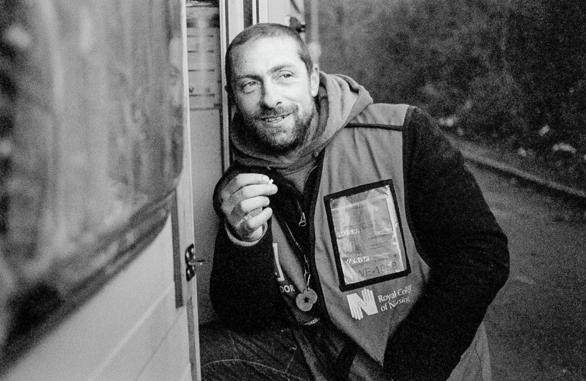 A homeless man leans on the step of his caravan looking away from the camera and smiling as he smokes a cigarette.