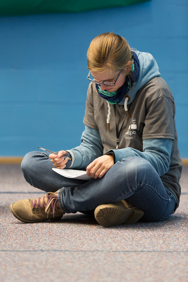 A female student sits alone, cross-legged on the floor with pen and paper.