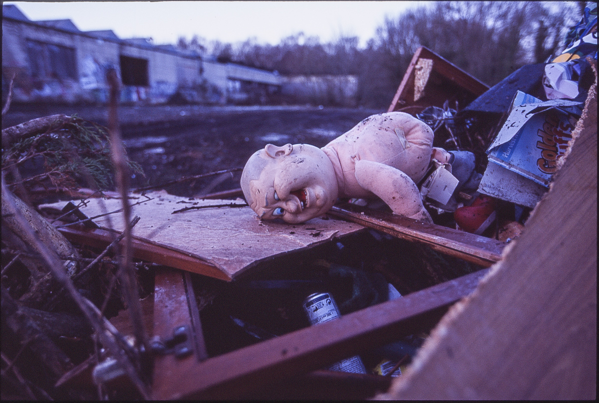 Colour photo of a peculiar naked male doll lying face-down on a pile of rubbish, an expression of horror/pain on its face.