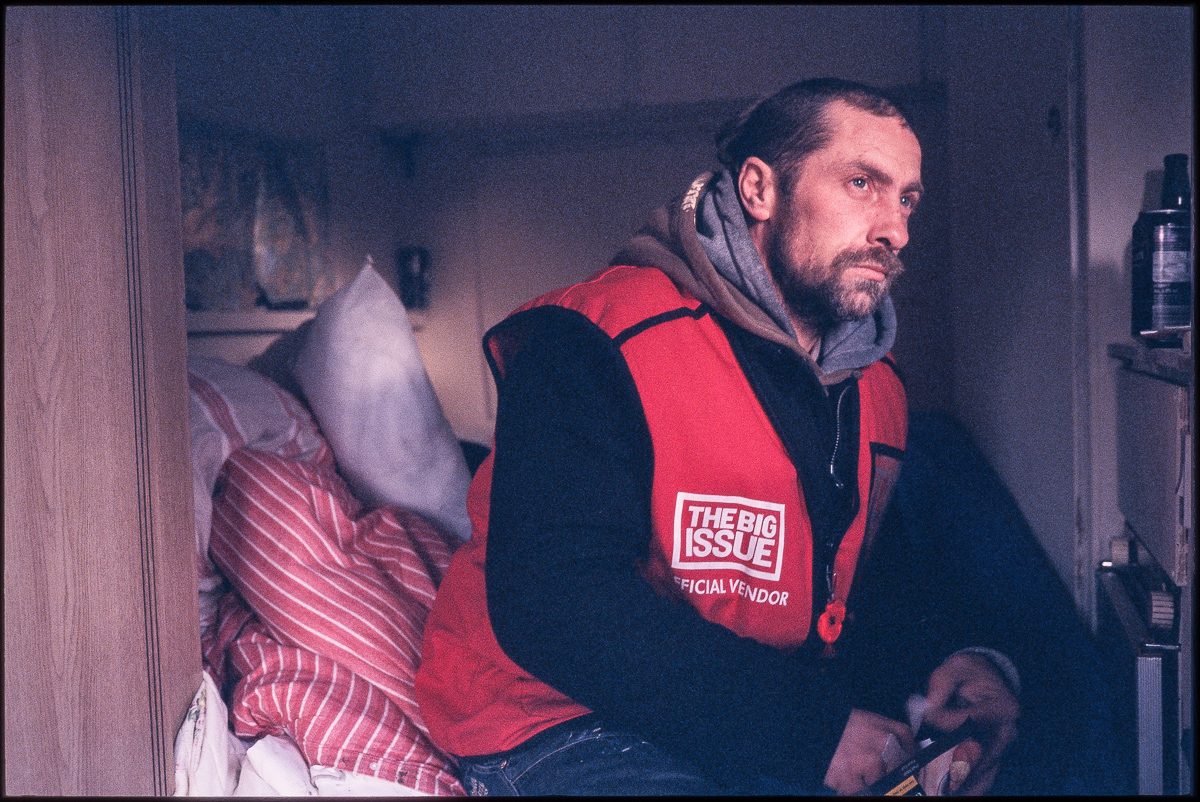 Colour portrait of Big Issue seller Alby wearing his red seller's vest, sitting inside his caravan looking to the right of the camera.