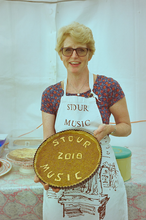 A bespectacled woman in a Stour Music Festival apron holds a tart for the view of the camera with the words Stour Music 2018 written out in pastry on its surface.