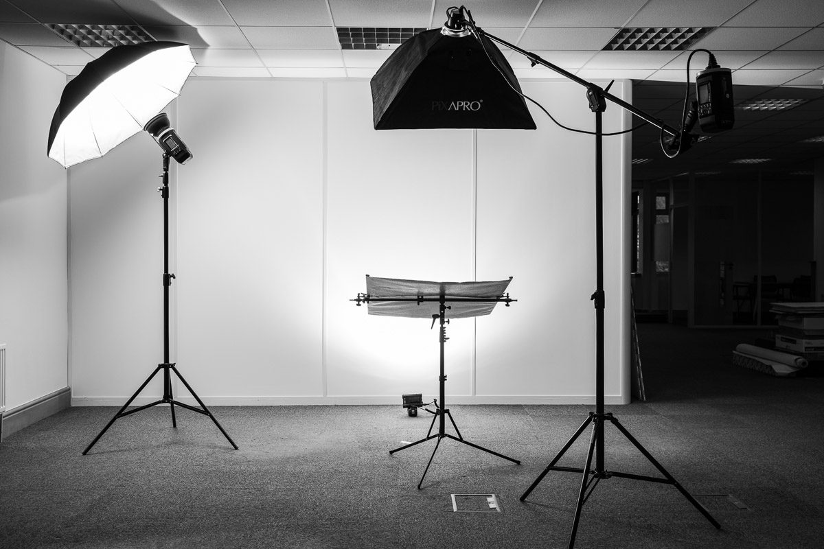 Photo shows a portable photographic studio lighting set up with three flash heads and a reflector in an empty office space.