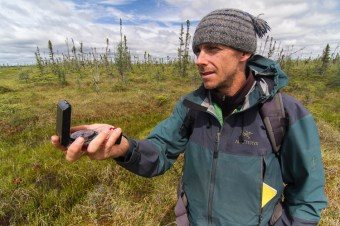 Tim Irvin takes a compass bearing while doing field research in Ontario's Far North.