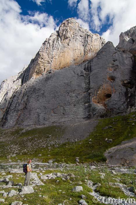 woman staring up at sheer valley walls near Mt MacDonald Yukon