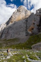 woman staring up at sheer valley walls near Mt MacDonald Yukon