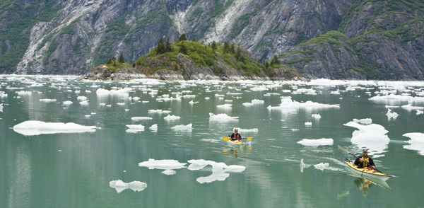 Two kayakers paddle amidst the ice and green waters of the BC coast.
