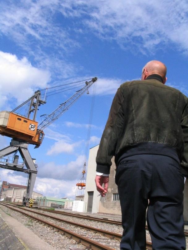 Ein Mann in Rückenansicht, im Hintergrund ein Kran