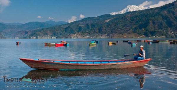 Man in boat on Lake Pokhara below Annapurna