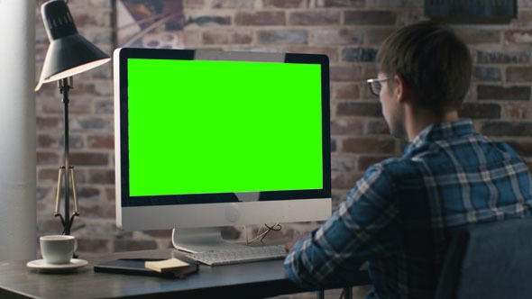 man working on computer with mock up green screen