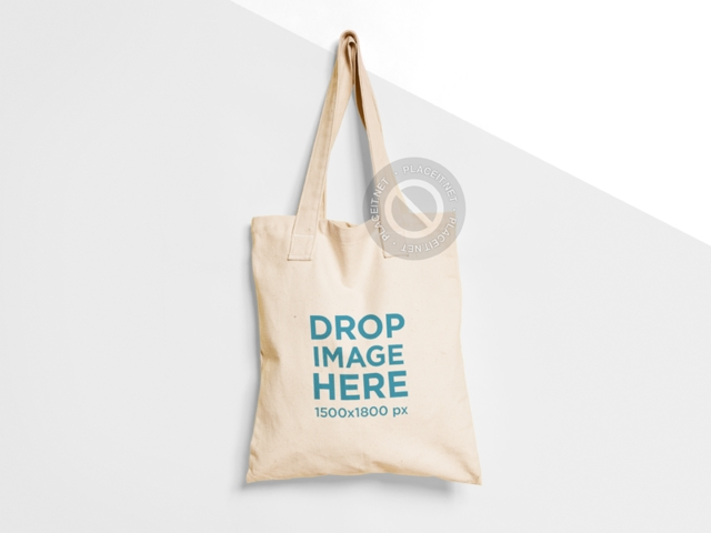 placeit tote bag mockup hanging from a nail on a two colors wall