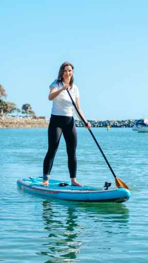 woman in white tank top and black leggings standing on blue and orange surfboard