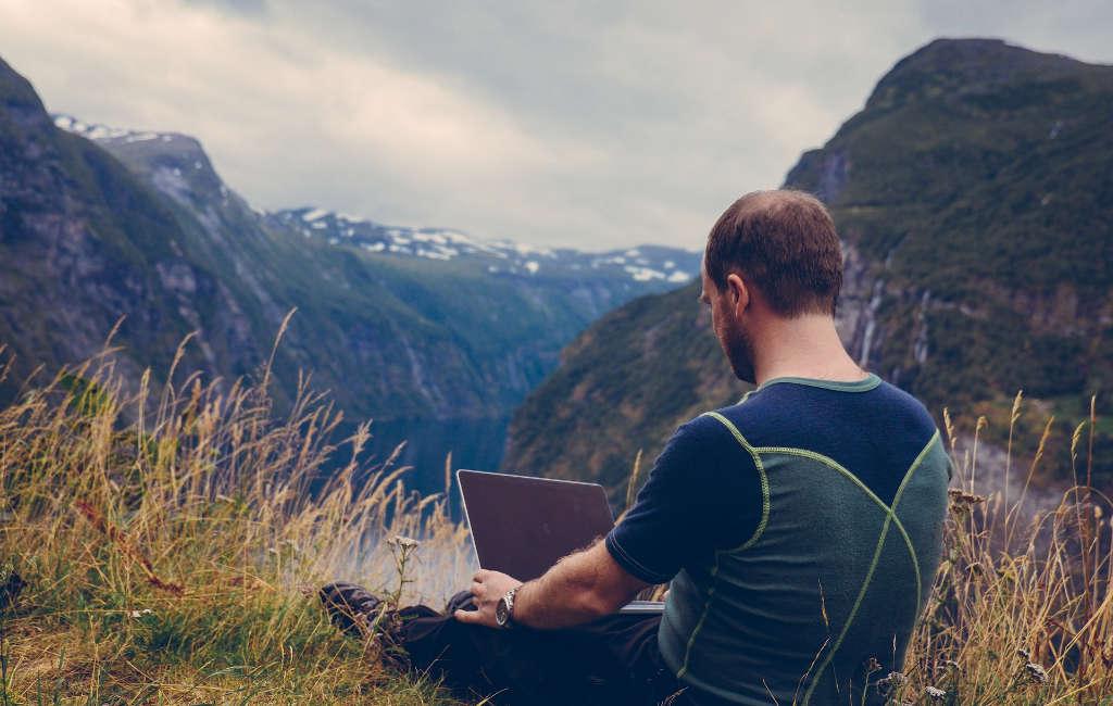 Hombre trabajando con el ordenador en el campo