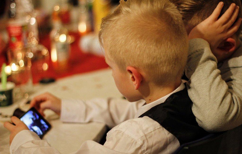 Niños entretenidos utilizando un teléfono móvil
