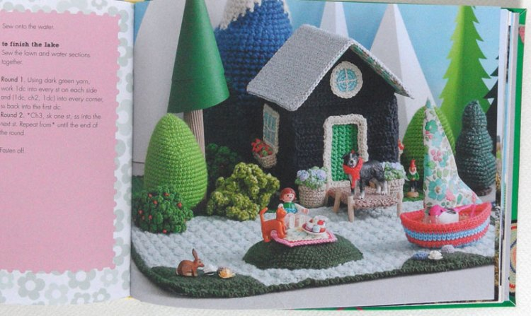 A crochet lakeside scene including cabin and sailboat, from Let's Go Camping by Kate Bruning