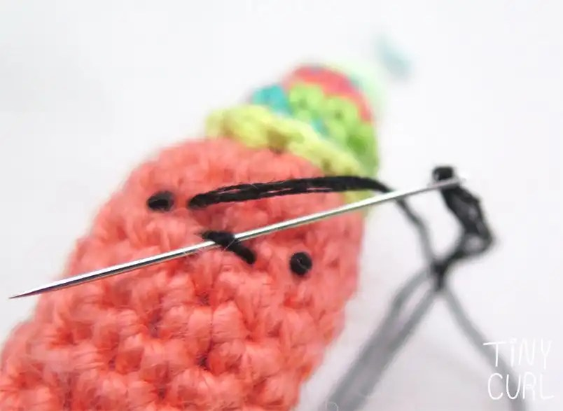 Party Snail amigurumi face embroidery up close mouth tutorial shot.