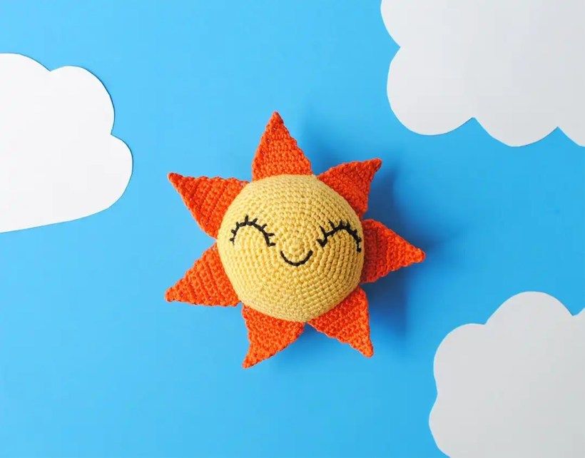 Picture of the aamigurumi Sun doll hanging with some clouds. Made with the free amigurumi crochet pattern by Tiny Curl.