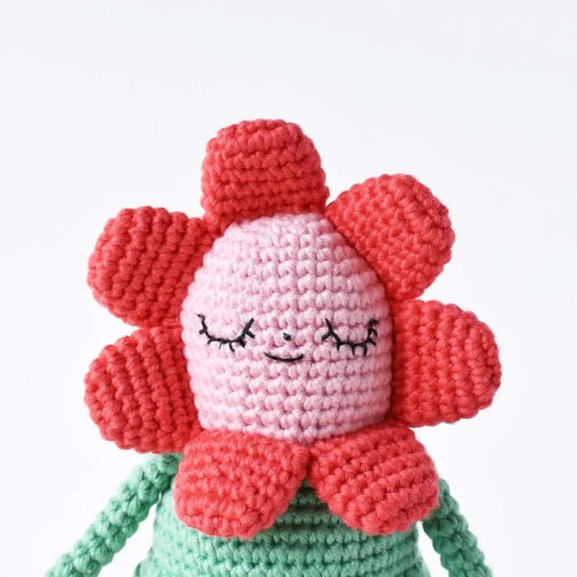 Up close image of Flower Gal's face in order to show detail of the amigurumi face embroidery.