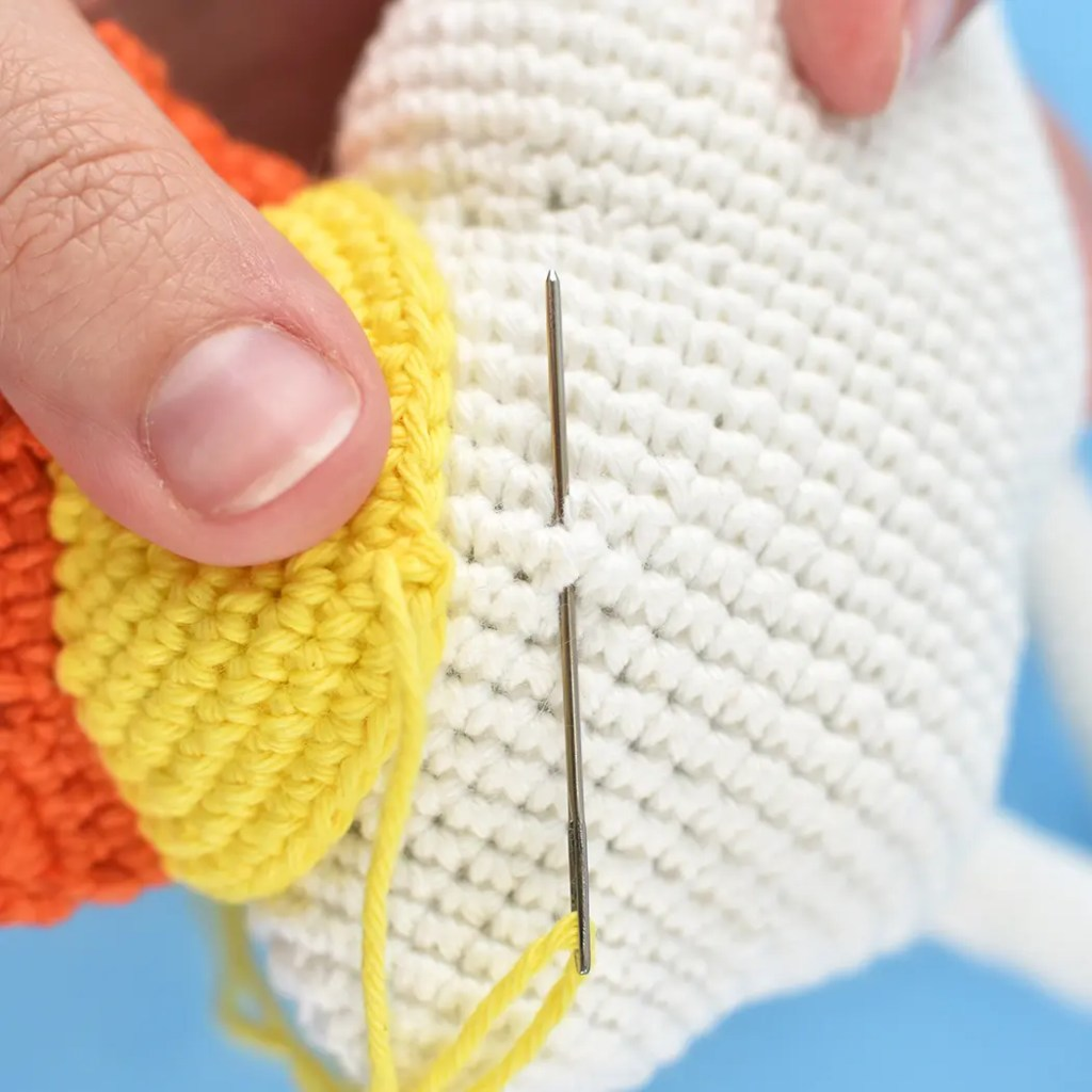 Showing how to attach and sew sun hat to top of crochet cloud using tapestry needle. A later step in the Rainbow Cloud Cutie amigurumi pattern.